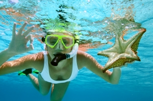 woman snorkeling with a starfish, showing the O.K. signal underwater